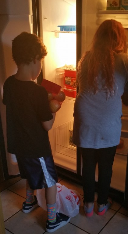 Brother and sister filling the fridge for the first time